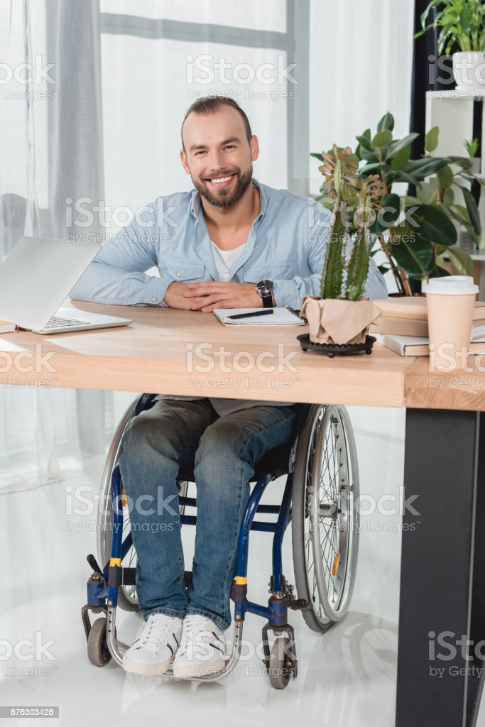man on wheelchair sitting at office stock photo