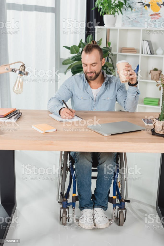 man on wheelchair sitting at worktable stock photo