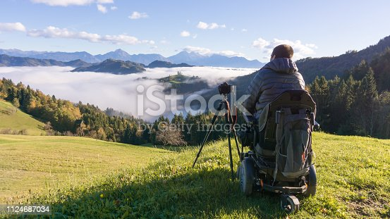 man on wheelchair taking photos of beautiful landscape