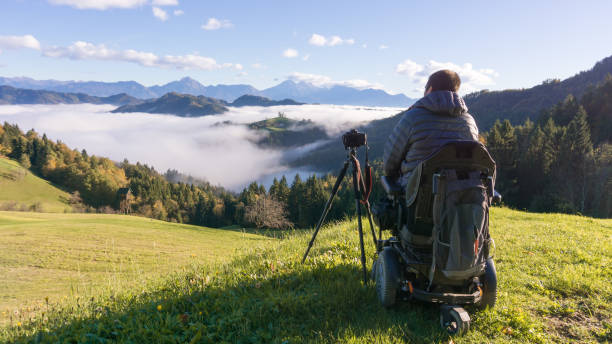 man on wheelchair taking photos of beautiful landscape in a foggy morning, St. Thomas Slovenia stock photo