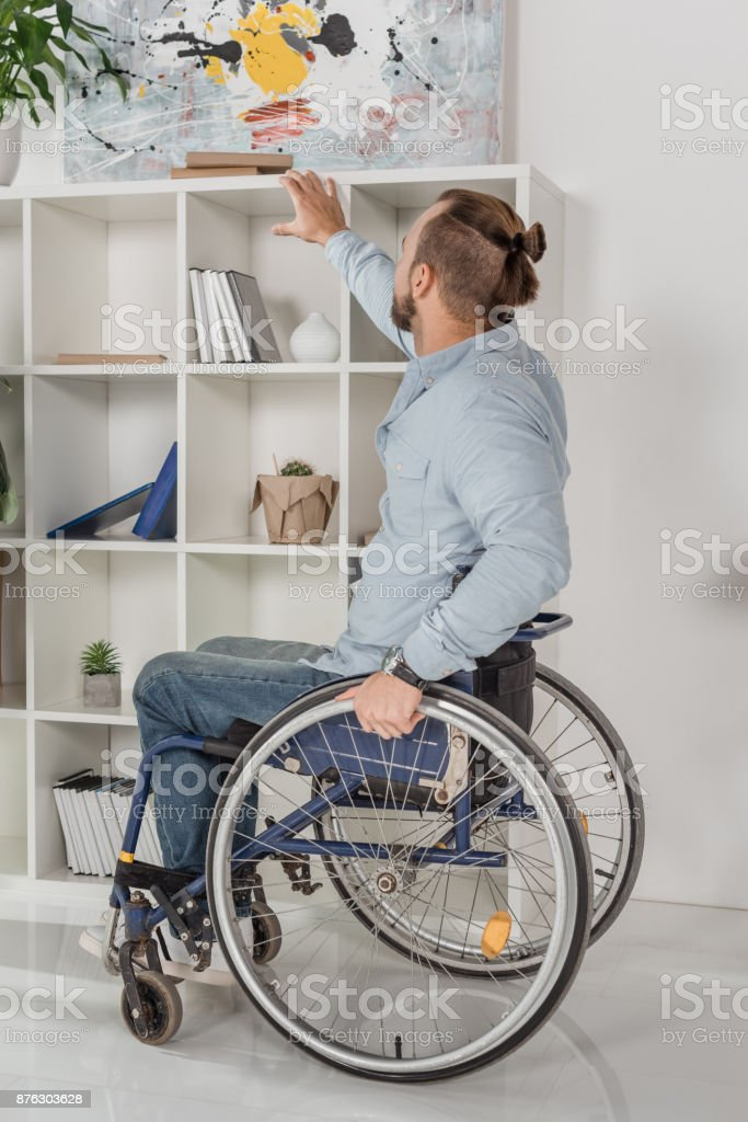 man on wheelchair trying to reach for book stock photo