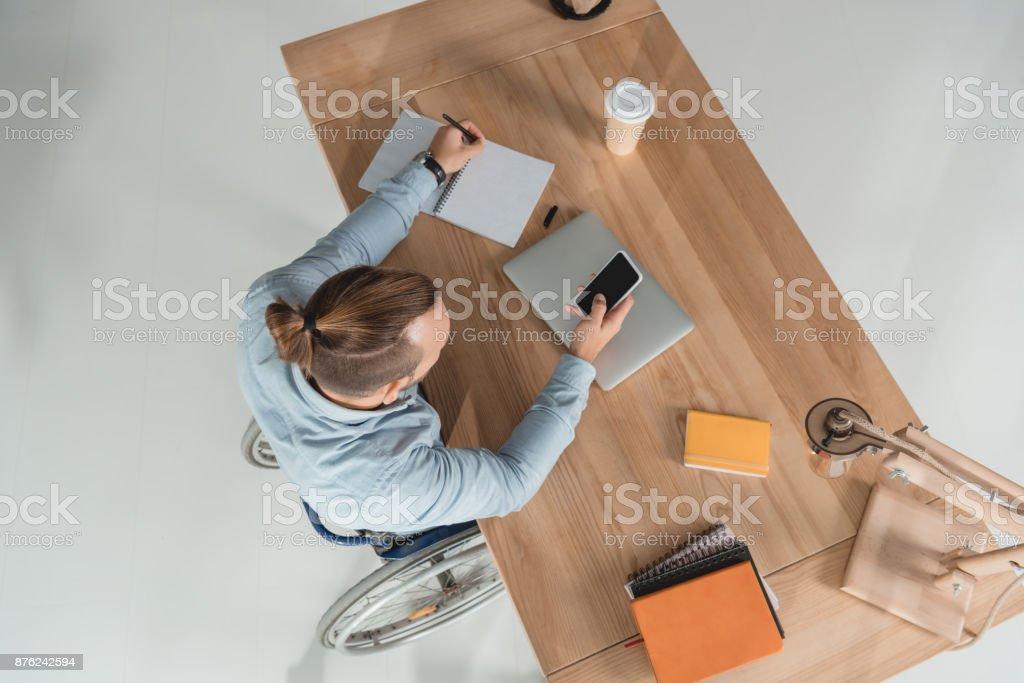 man on wheelchair using smartphone stock photo