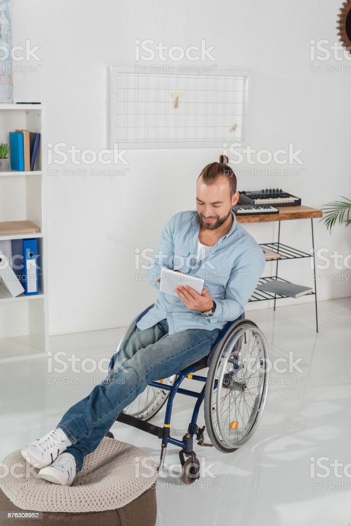 man on wheelchair using tablet stock photo