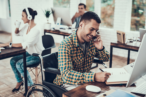 Man on Wheelchair Write Notes and Talking on Phone