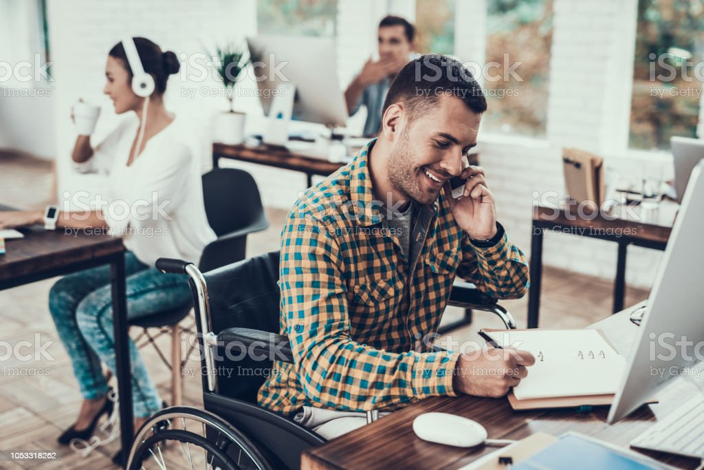 Man on Wheelchair Write Notes and Talking on Phone stock photo