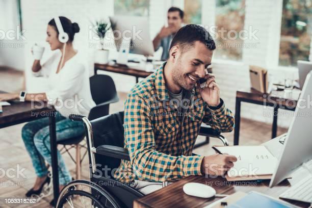 Man On Wheelchair Write Notes And Talking On Phone - Fotografias de stock e mais imagens de Adulto