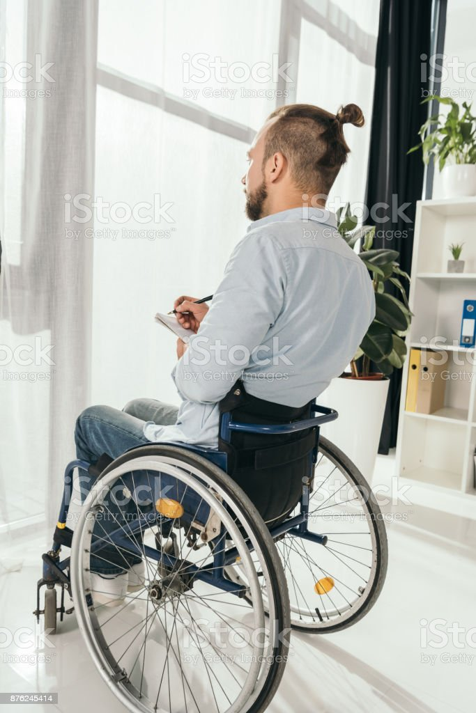 man on wheelchair writing in notebook stock photo