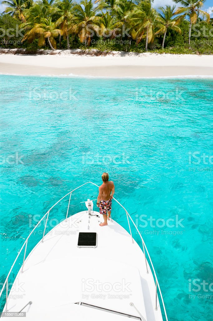 man on yacht approaching Caribbean island with palm trees royalty-free stock photo
