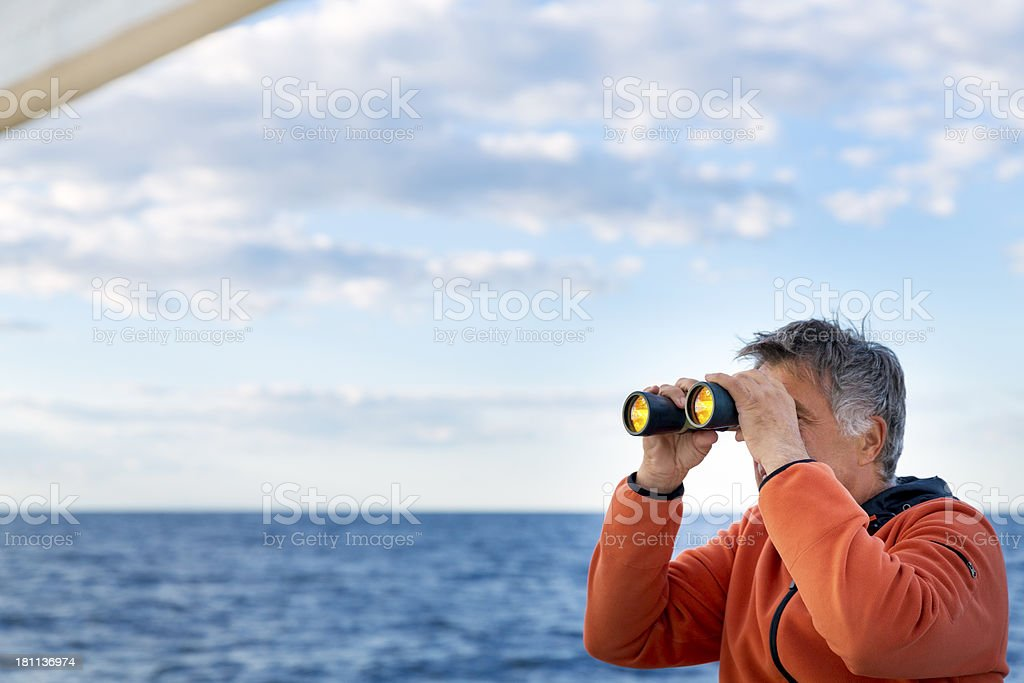 Man on yacht  looks through binoculars stock photo