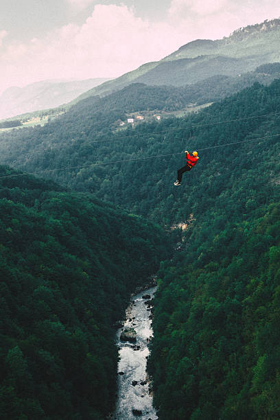 Man on zip line under the Tara river Man in red coat on zip line under the Tara river Gorge  zip line stock pictures, royalty-free photos & images