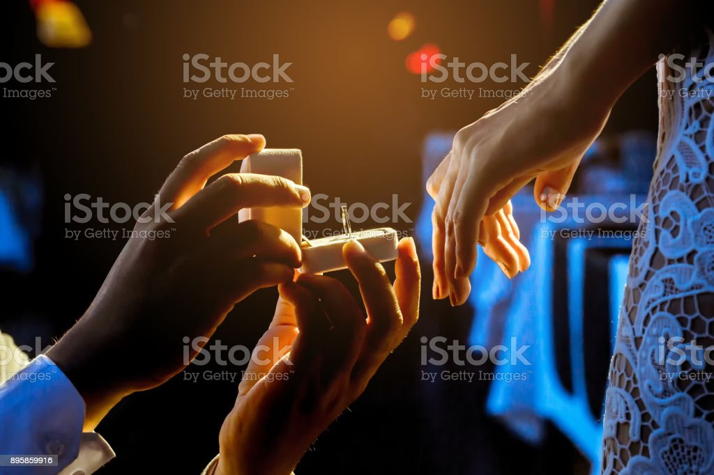 Man open a ring box to give a gift to his girlfriend. stock photo