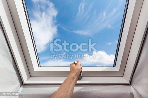 966792200 istock photo Man open new skylight (mansard window) in an attic room against blue sky 897277204