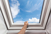 Man open new skylight (mansard window) in an attic room against blue sky