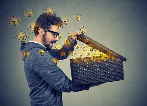 istock man opening a box with many bright light bulbs 934271090