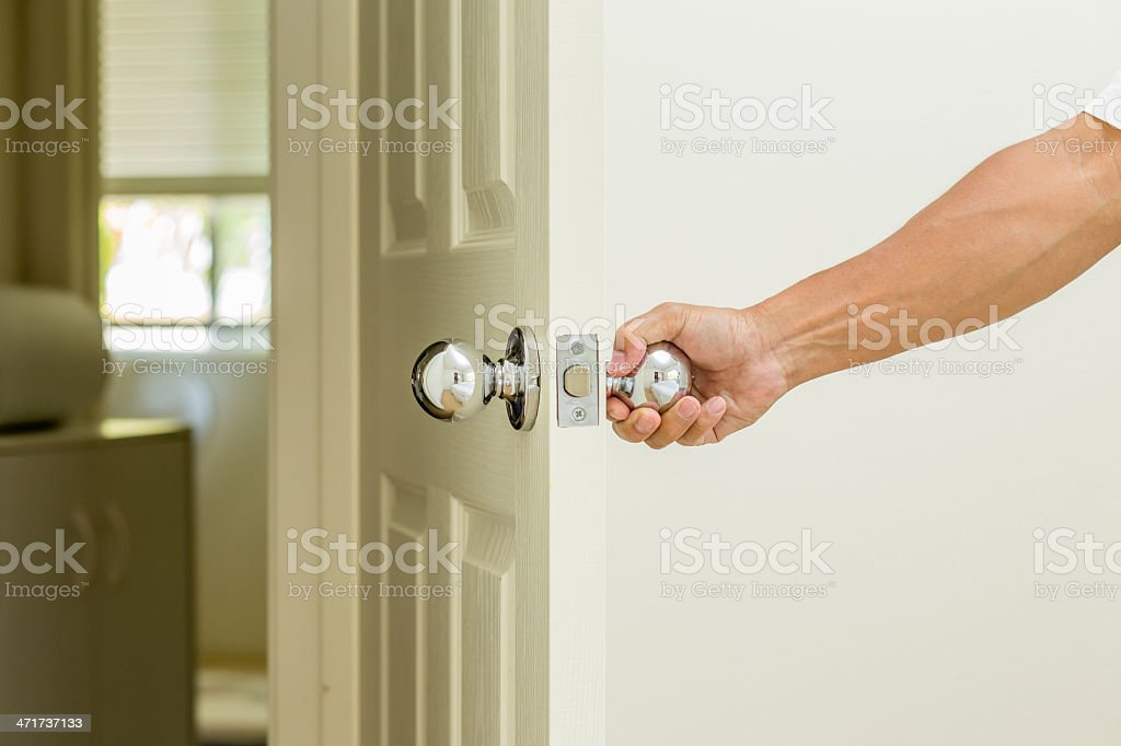 A man opening a door by turning the knob stock photo