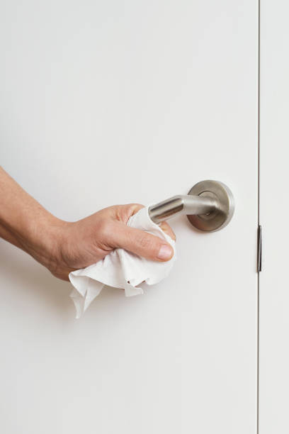 man opening a door using a disinfecting wipe stock photo
