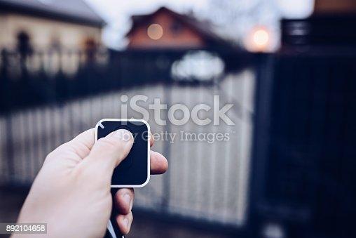 istock Man opening automatic property gate 892104658