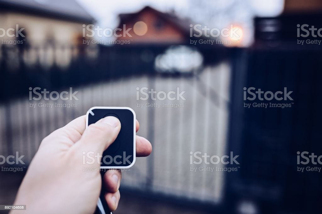 Man opening automatic property gate stock photo