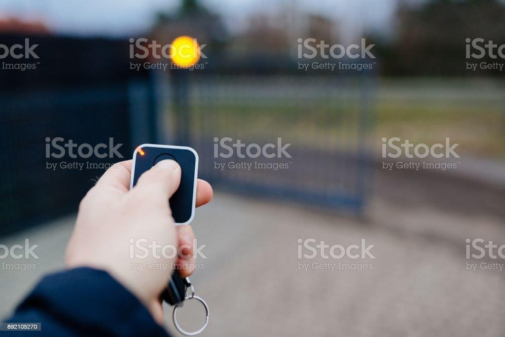 Man opening automatic property gate stock photo