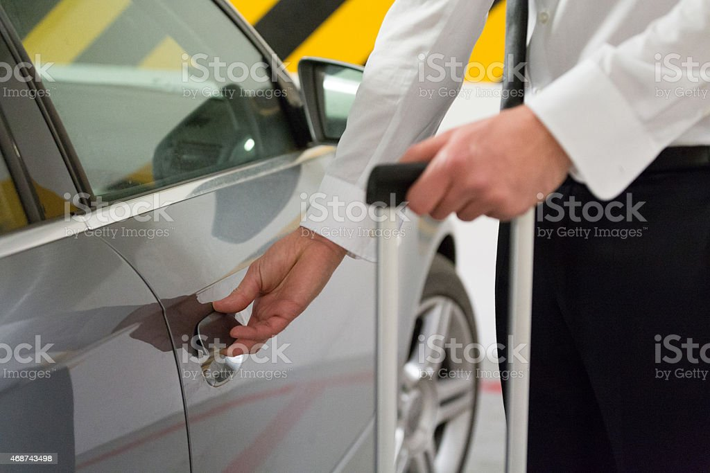 Man opening car door Businessman wearing shirt and tie opening a door to the silver car parked in the garage. Close up of hands, unrecognizable person. 2015 Stock Photo