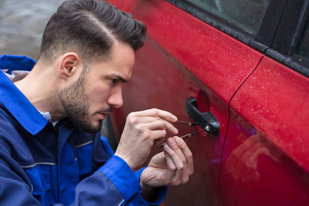 Man Opening Car Door With Lockpicker Young Man Opening Red Car Door With Lockpicker locksmith stock pictures, royalty-free photos & images