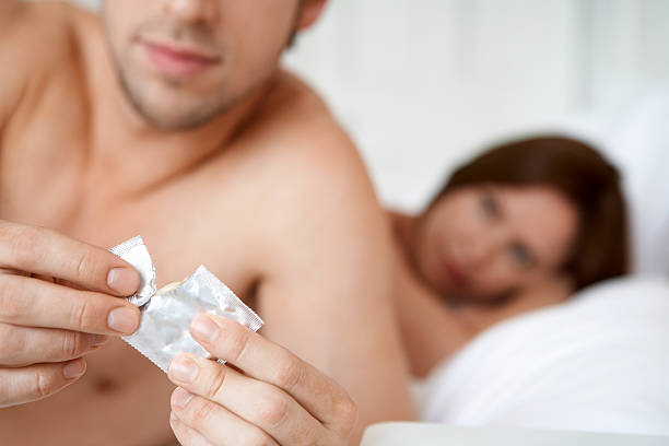 man opening condom with woman in bed - rubber stock photos and pictures