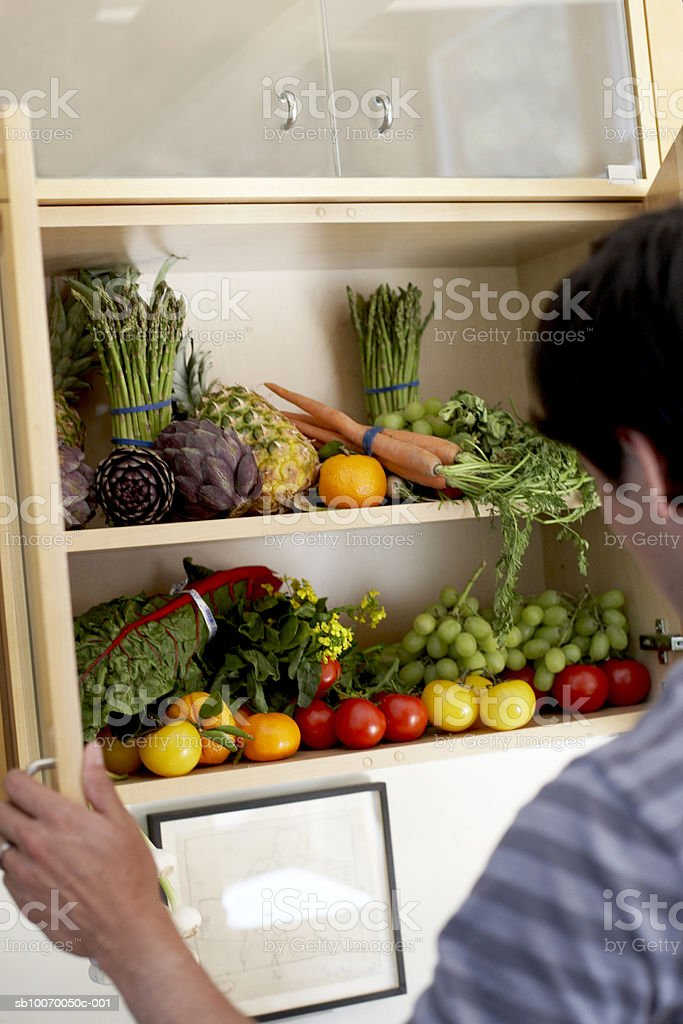 Man opening cupboard filled with vegetables and fruits, rear view royalty-free stock photo
