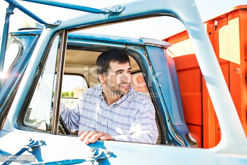 Farmer opening door to get out of colorful old farm truck.