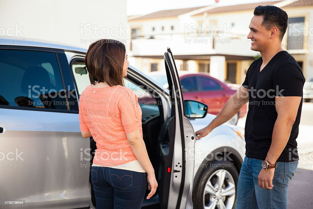 Man opening door to woman stock photo