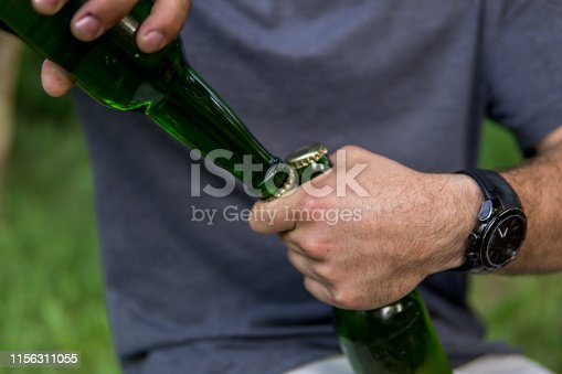 Opening beer bottles in nature without a beer opener, using one bottle to open another bottles, close up of male hands, nature picnic, holiday
