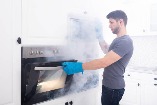 man opening oven filled with smoke - burned oven imagens e fotografias de stock