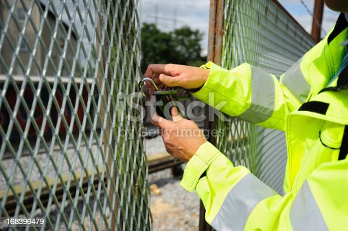 Subway area, man opening the locked wire fence, removing lock and chain.