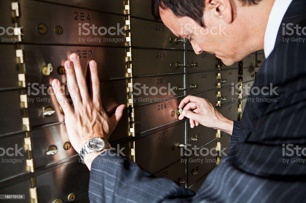 Man opening safety deposit box stock photo