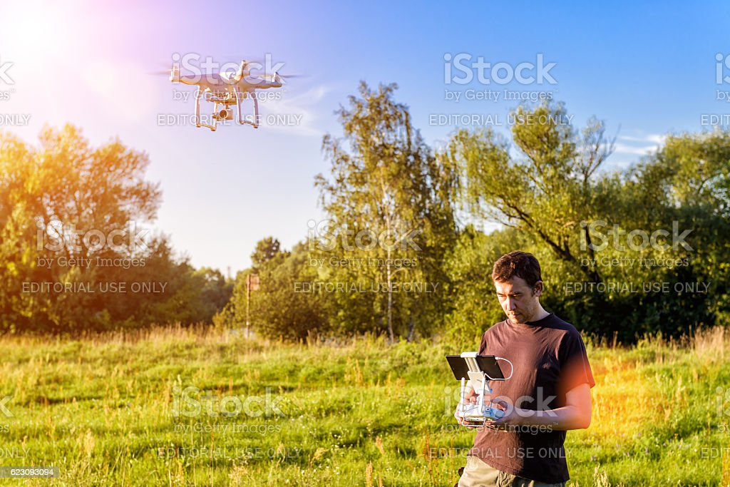 Man operating a drone quad copter - Photo