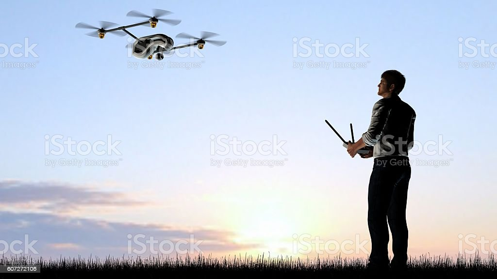 Man operating a drone quadrocopter at sunset using a controller – Foto