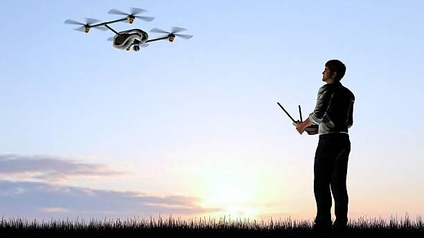man operating a drone quadrocopter at sunset using a controller - flugdrohne stock-fotos und bilder
