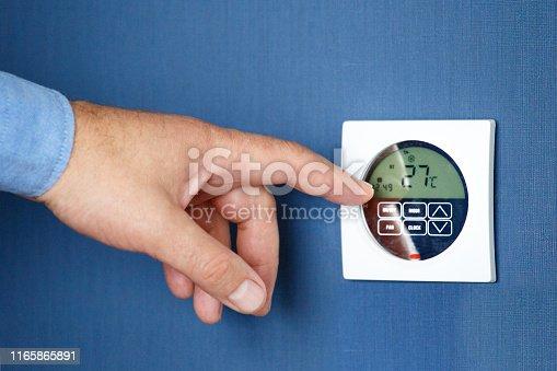 527550426istockphoto Man operating air conditioner. 1165865891