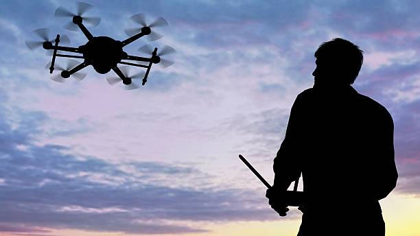 man operating of flying drone multicopter UAV at sunset – Foto