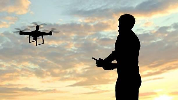 mann betrieb des fliegens hintergrundgeräusche quadrocopter während dem sonnenuntergang - flugdrohne stock-fotos und bilder