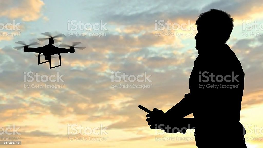 man operating of flying drone quadrocopter at sunset stock photo