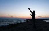 Silhouette of man operating drone quadcopter Dji Phantom 4 at sunset in Antalya, Side Turkey 23 May 17.