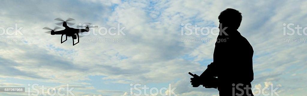 Mann Betrieb des fliegend Hintergrundgeräusche quadrocopter in der Himmel – Foto