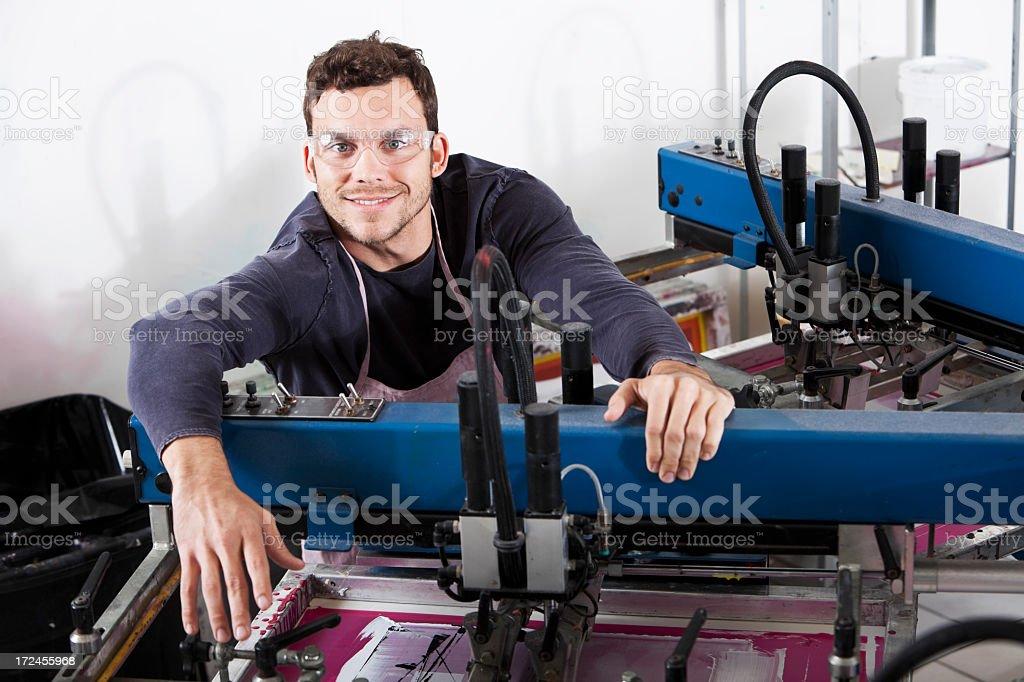Man operating screen printing equipment stock photo