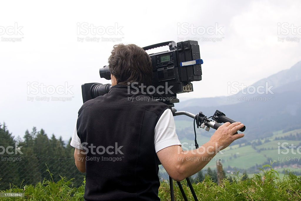 Man operating video camera in mountains stock photo