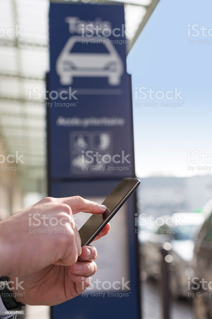 Man orders a taxi from his mobile phone. Close-up hands stock photo