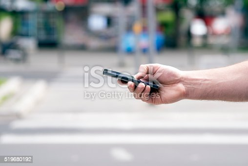 istock man orders a taxi from his mobile phone 519680192