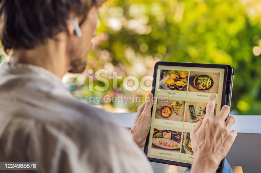 man orders food for lunch online using Tablet.