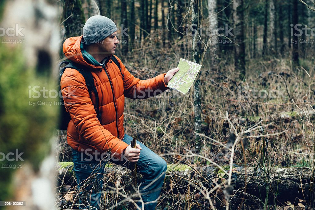 Man orienteering in woods in winter and looking at map stock photo