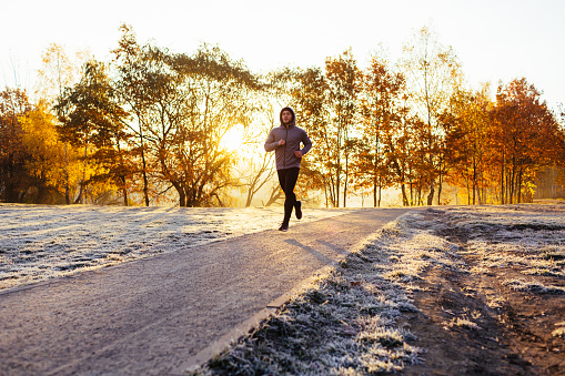 Man out running in the park on sunny autumn morning