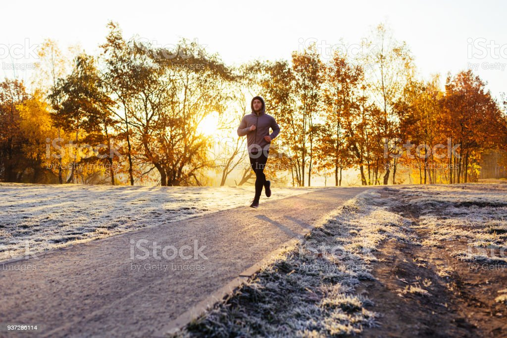 Man out running in the park on sunny autumn morning stock photo